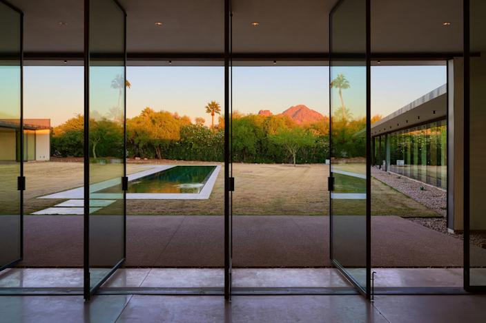 With views of Camelback Mountain and Piestewa Peak, this Arizona house features dramatic spaces constructed with exposed concrete and raw steel. The home was inspired by the work of Pritzker Prize–winning Australian architect Glenn Murcutt and was designed to work with the surrounding landscape and maximize natural light. The property boasts a 25-meter lap pool, a hot tub, and a five-car garage.
