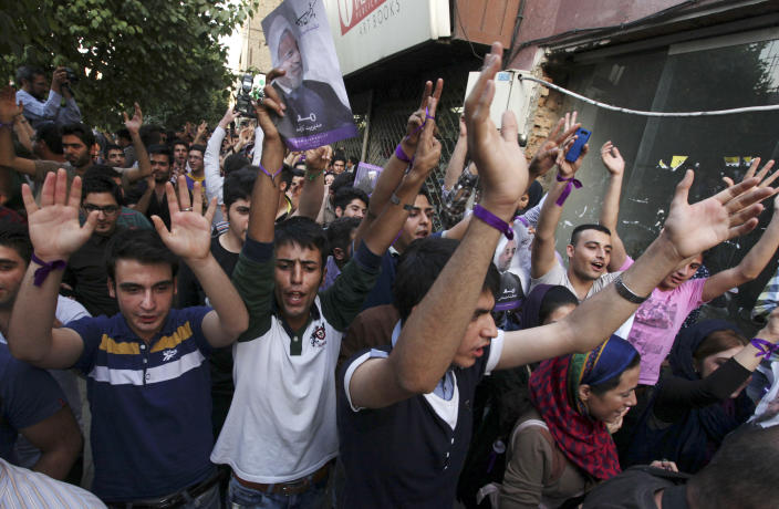 Supporter of the Iranian presidential candidate Hasan Rowhani celebrate outside his campaign headquarters in Tehran, Iran, Saturday, June 15, 2013. Moderate cleric Hasan Rowhani was declared the winner of Iran's presidential vote on Saturday after gaining support among many reform-minded Iranians looking to claw back a bit of ground after years of crackdowns. (AP Photo/Vahid Salemi)