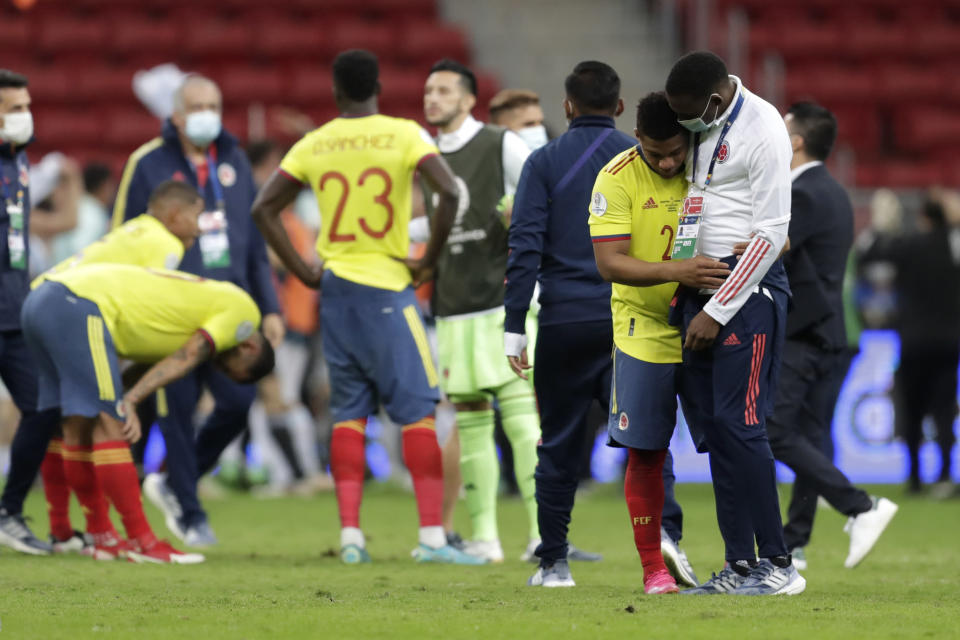 Colombia's Yimmi Chara, second right, is comfort by a member of the team after Argentina defeated Colombia in a penalty shootout during a Copa America semifinal soccer match at the National stadium in Brasilia, Brazil, Wednesday, July 7, 2021. (AP Photo/Eraldo Peres)
