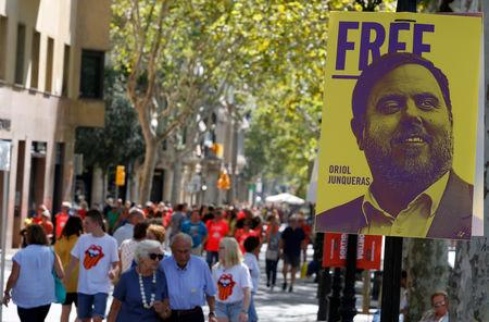 FILE PHOTO: People walk past a banner depicting dismissed Catalan Vice President Oriol Junqueras, currently in custody awaiting trial on charges of sedition, rebellion and misappropriation of public funds, during Catalonia's national day 'La Diada' in Barcelona, Spain, September 11, 2018. REUTERS/Enrique Calvo -/File Photo