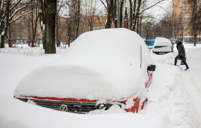 A pedestrian walks near cars covered with snow in a street in Moscow
