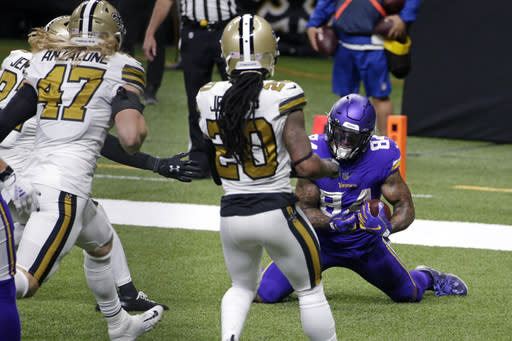 Minnesota Vikings tight end Irv Smith (84) pulls in a touchdown reception in front of New Orleans Saints cornerback Janoris Jenkins (20), middle linebacker Alex Anzalone (47) and strong safety Malcolm Jenkins (27) in the second half of an NFL football game in New Orleans, Friday, Dec. 25, 2020. (AP Photo/Butch Dill)
