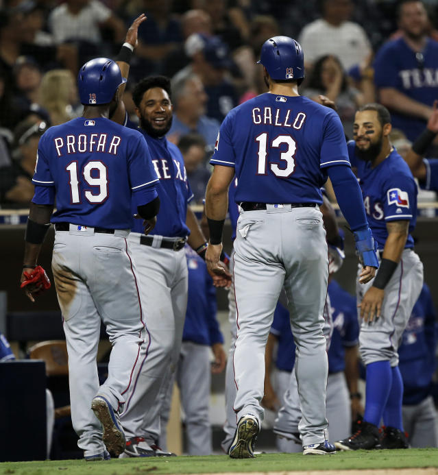 Texas Rangers' Jurickson Profar (19) and Joey Gallo (13) get congratulations from Elvis Andrus, second from left, and Rougned Odor, right, after scoring with Adrian Beltre on a three-run double by Robinson Chirinos during the sixth inning of a baseball game against the San Diego Padres in San Diego, Saturday, Sept. 15, 2018. (AP Photo/Alex Gallardo)
