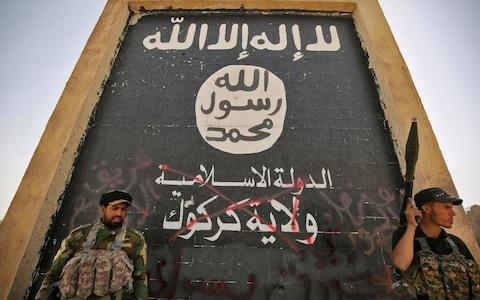Fighters from the Hashed al-Shaabi (Popular Mobilisation units), backing the Iraqi forces, stand in front of a mural depicting the emblem of the Islamic State (Isil) group as troops advance through Hawija - Credit: AFP