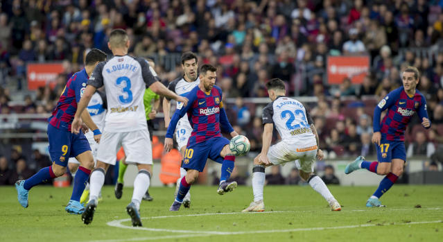 Barcelona's Lionel Messi, center, controls the ball during a Spanish La Liga soccer match between Barcelona and Alaves at Camp Nou stadium in Barcelona, Spain, Saturday, Dec. 21, 2019. (AP Photo/Joan Monfort)