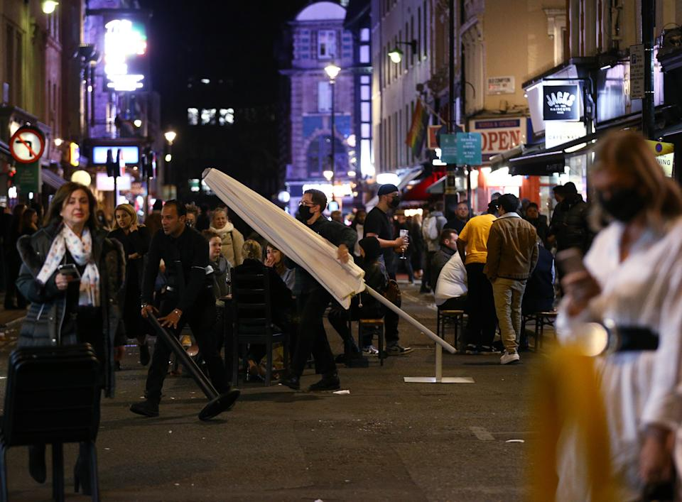Bar staff begin clearing street furniture ahead of closing time in Soho, London, after pubs and restaurants were subject to a 10pm curfew to combat the rise in coronavirus cases in England.