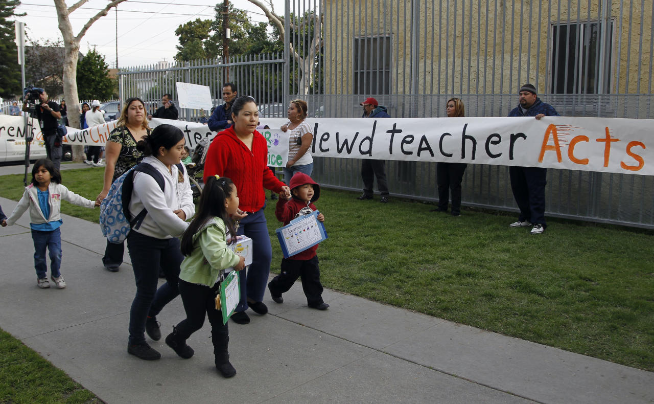 Parents bring their children to school as others protest outside Miramonte Elementary school in Los Angeles Monday, Feb. 6, 2012. About three dozen parents and supporters staged a protest at the Los Angeles-area school rocked by allegations of lewd conduct crimes by two teachers against children. They demanded greater communication with education officials and the placement of cameras in classrooms and hallways at Miramonte Elementary School. (AP Photo/Damian Dovarganes)