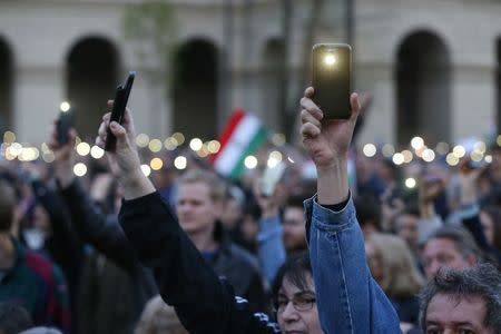 People light with their mobile phones  as they protest against the bill that would undermine Central European University in Budapest