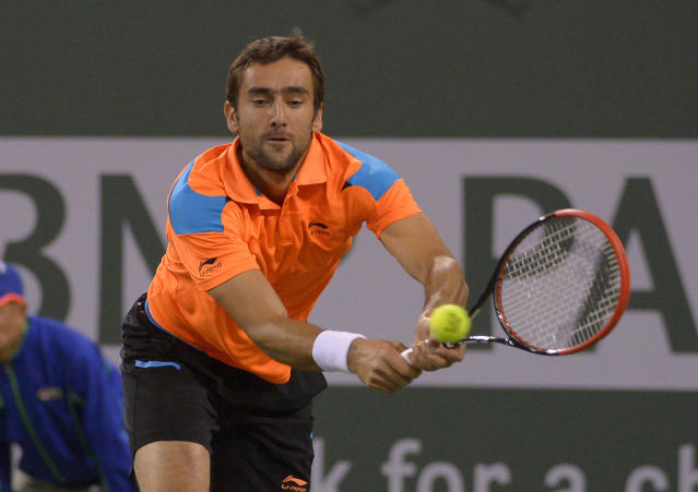 Marin Cilic, of Croatia, returns a shot to Novak Djokovic, of Serbia, during their match at the BNP Paribas Open tennis tournament, Wednesday, March 12, 2014, in Indian Wells, Calif. (AP Photo/Mark J. Terrill)