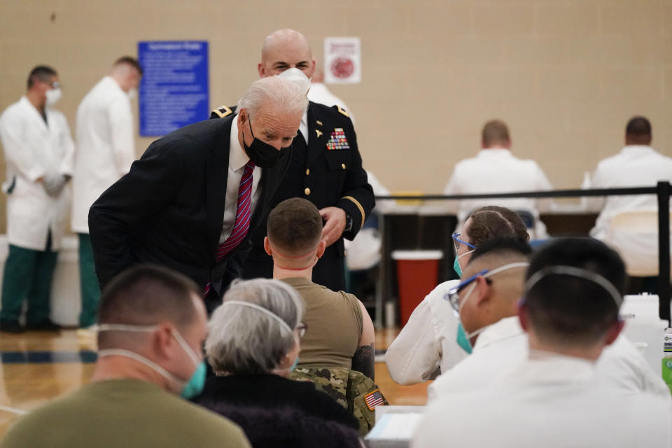 President Joe Biden speaks with a service member as he tours the COVID-19 vaccine center at Walter Reed National Military Medical Center with Col. Andrew Barr, director of Walter Reed, Friday, Jan. 29, 2021, in Bethesda, Md. (AP Photo/Alex Brandon)