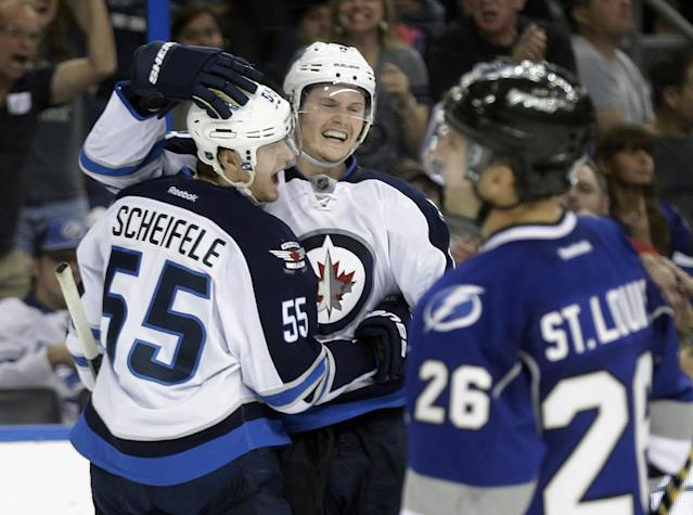 Winnipeg Jets center Mark Scheifele (55) celebrates his overtime goal against the Tampa Bay Lightning with teammate defenseman Jacob Trouba (8) during an NHL hockey game Saturday, Dec. 7, 2013, in Tampa, Fla. The Jets won the game 2-1. Skating away is Lightning's Martin St. Louis (26). (AP Photo/Chris O'Meara)