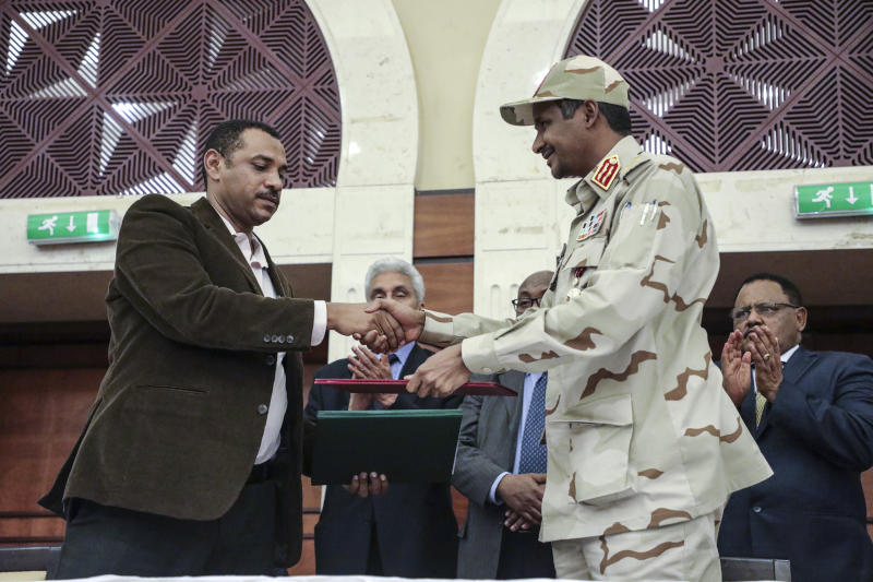 Gen. Mohammed Hamdan Dagalo, right, and Sudan's pro-democracy movement leader Ahmad al-Rabiah shake hands after signing a power sharing document in Khartoum, Sudan, Wednesday, July 17, 2019. The two sides are still at work on a more contentious constitutional agreement that would specify the division of powers. (AP Photo/Mahmoud Hjaj)