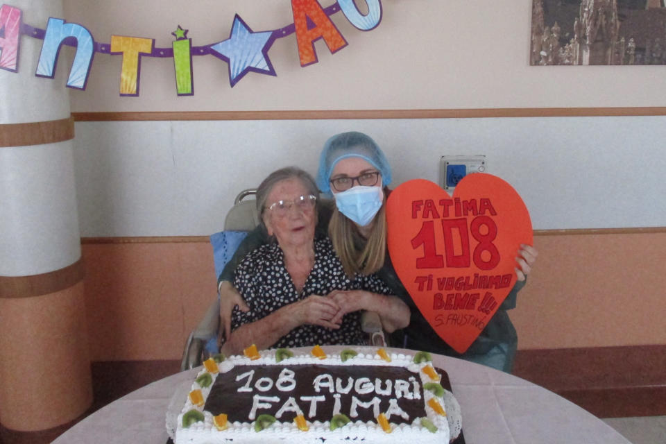 "In this photo taken on Wednesday, June 3, 2020, Fatima Negrini, left, is flanked by nurse Laura Catena holding a cut out heart reading in Italian "" Fatima 108, we love you "" while posing in front of a cake celebrating her 108th birthday, at the Anni Azzurri San Faustino nursing home, in Milan, Italy. Fatima Negrini has joined the ranks of the very few centenarians who have recovered from COVID-19. (RSA Anni Azzurri San Faustino via AP)"