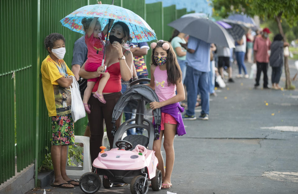 People wait in line outside a public school to get a shot of China's Sinovac CoronaVac vaccine in Serrana, Sao Paulo state, Brazil, Wednesday, Feb. 17, 2021. Brazil's Butantan Institute has started a mass vaccination on Wednesday of the city's entire adult population, about 30,000 people, to test the virus' behavior in response to the vaccine. (AP Photo/Andre Penner)