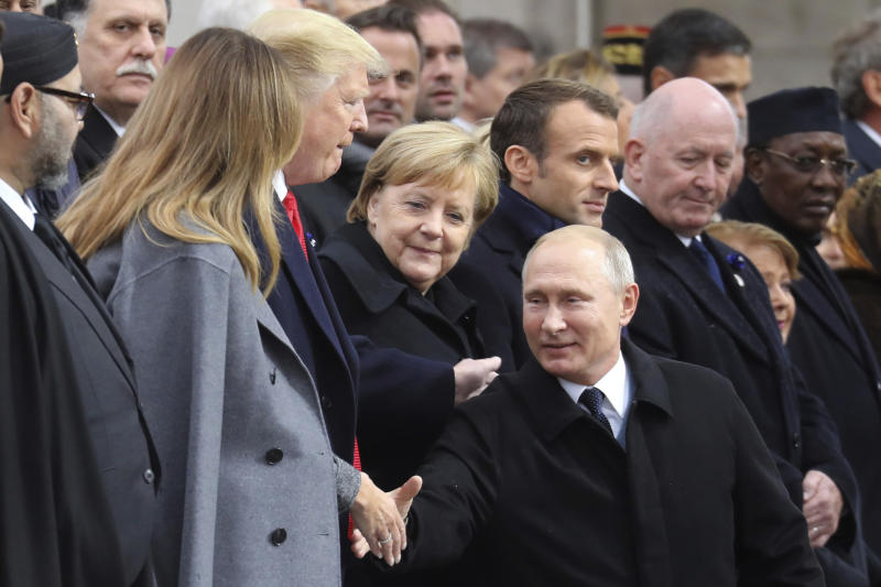Russian President Vladimir Putin shakes hands with US First Lady Melania Trump, left, next to US President Donald Trump, German Chancellor Angela Merkel and French President as he arrives to attend a ceremony at the Arc de Triomphe in Paris as part of commemorations marking the 100th anniversary of the 11 November 1918 armistice, ending World War I, Sunday, Nov. 11, 2018. (Ludovic Marin/Pool Photo via AP)
