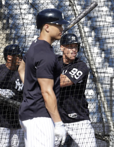 New York Yankees' Aaron Judge, right, hits as Giancarlo Stanton, center, looks on during batting practice before a baseball spring exhibition game against the Detroit Tigers, Wednesday, Feb. 28, 2018, in Tampa, Fla. (AP Photo/Lynne Sladky)