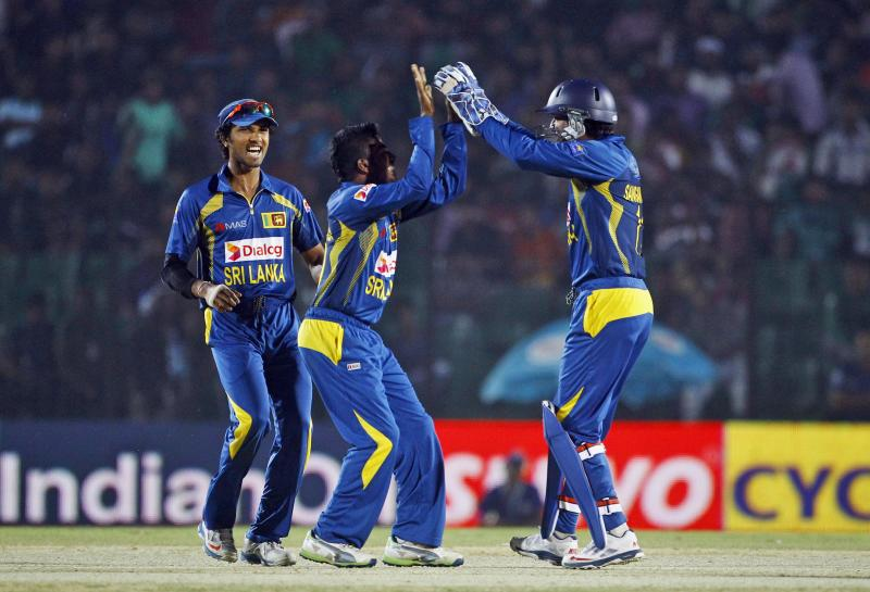 Sri Lanka's Chaturanga de Silva, center, celebrates the wicket of Pakistan's Ahmed Shehzad with teammates during the opening match of the Asia Cup one-day international cricket tournament between them in Fatullah, near Dhaka, Bangladesh, Tuesday Feb. 25, 2014. (AP Photo/A.M. Ahad)