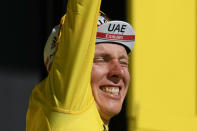 Slovenia's Tadej Pogacar, wearing the overall leader's yellow jersey, celebrates on the podium after the twentieth stage of the Tour de France cycling race, an individual time-trial over 30.8 kilometers (19.1 miles) with start in Libourne and finish in Saint-Emilion, France, Saturday, July 17, 2021. (AP Photo/Daniel Cole)