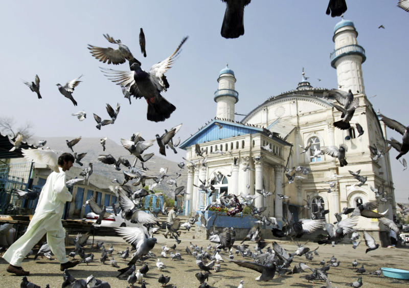 Pigeons fly outside the Shah-e Doh Shamshira mosque as Afghans head for morning prayers on Eid-al-Fitr in Kabul, Afghanistan, Thursday, August, 8, 2013. Eid al-Adha is a religious festival celebrated by Muslims worldwide at the end of the holy fasting month of Ramadan. (AP Photo/Ahmad Nazar)