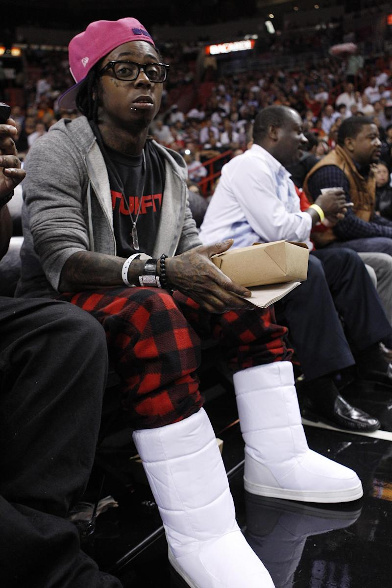 """FILE - In this Jan. 27, 2012 file photo, Rapper Lil Wayne sits courtside during an NBA basketball game between the Miami Heat and New York Knicks, in Miami. The Thunder say Lil Wayne is welcome to attend a playoff game in Oklahoma City, but needs to buy a ticket just like everyone else. The rapper created a stir Thursday, May 31, 2012 by posting on Twitter that he was """"going to go to the Thunder game tonight but was denied by the team to be in their arena."""" (AP Photo/Lynne Sladky, File)"""