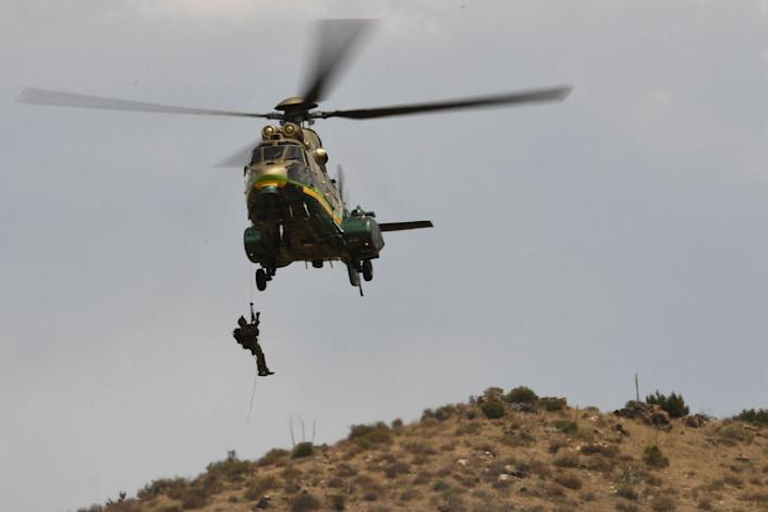 A man dangles from a cable attached to a helicopter hovering over a hillside.