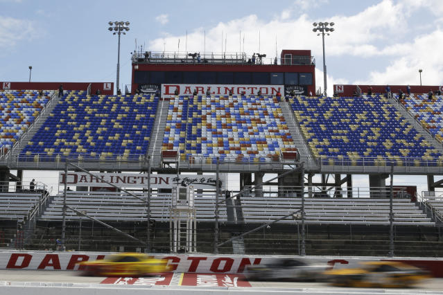 Cars pass by empty seats during the NASCAR Cup Series auto race Sunday, May 17, 2020, in Darlington, S.C. (AP Photo/Brynn Anderson)