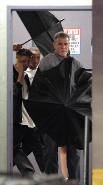 Justin Bieber, left, leaves his lawyers office in Miami, Thursday, March 6, 2014, after testifying in a civil deposition regarding an alleged assault on a photographer last year. (AP Photo/Luis M. Alvarez)