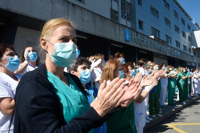 Healthcare workers applaud in return as they are cheered on by local police outside the University Hospital in Coruna, north-west Spain. (Getty Images)