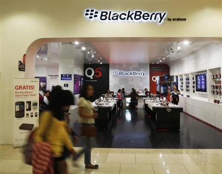 Passers-by walk in front of a BlackBerry service centre in Jakarta