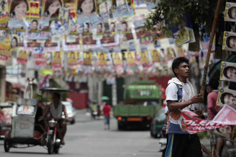 A government worker cuts down rows of election posters outside a school used as a voting center during the mid-term elections in Manila, Philippines on Tuesday, May 14, 2013. Former President Joseph Estrada was proclaimed Tuesday as the new mayor of the Philippine capital, Manila, his first elected post since his ouster in an anti-corruption revolt 12 years earlier.(AP Photo/Aaron Favila)