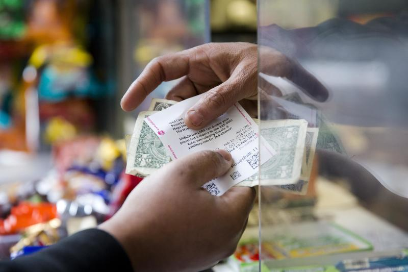 Atul Amin, right, sells Powerball tickets at his news stand Wednesday, Feb. 19, 2014, in Philadelphia. The estimated Powerball lottery jackpot is $400 million. (AP Photo/Matt Rourke)