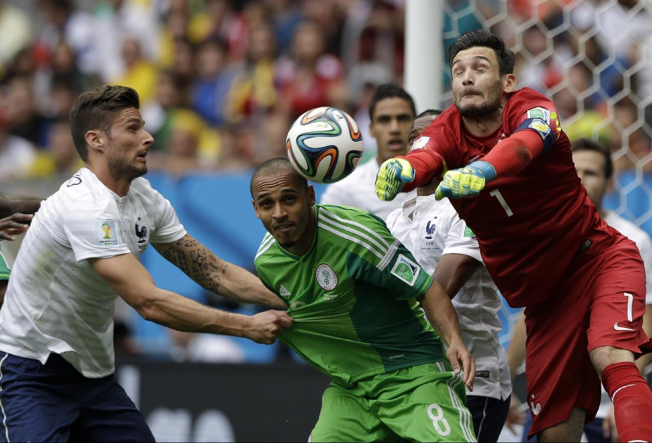 France's goalkeeper Hugo Lloris, right, punches the ball as teammate Olivier Giroud, left, grabs Nigeria's Peter Odemwingie's jersey during the World Cup round of 16 soccer match between France and Nigeria at the Estadio Nacional in Brasilia, Brazil, Monday, June 30, 2014. (AP Photo/Ricardo Mazalan)