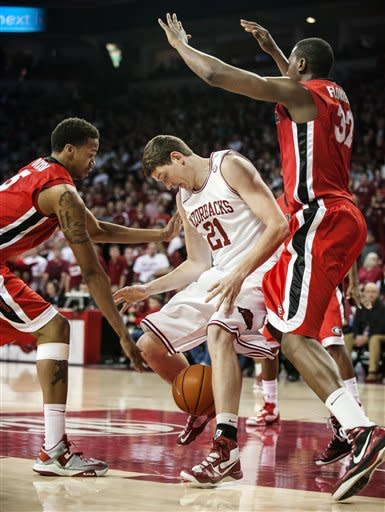 Arkansas' Hunter Mickelson (21) tries to regain possession of the ball as Georgia's Tim Dixon, left, and John Florveus (32) defend during the first half of an NCAA college basketball game in Fayetteville, Ark., Thursday, Feb. 21, 2013. (AP Photo/April L. Brown)