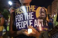 FILE - In this July 17, 2021, file photo, a person holds a candle and a poster with an image of the late Rep. John Lewis during a rally in support of voting rights, at Black Lives Matter Plaza in Washington. In the nation's capital on Saturday, Aug. 28, 2021, multiracial coalitions of civil, human and labor rights leaders are convening rallies and marches to urge passage of federal voter protections that have been eroded since the Voting Rights Act of 1965. (AP Photo/Jose Luis Magana, File)