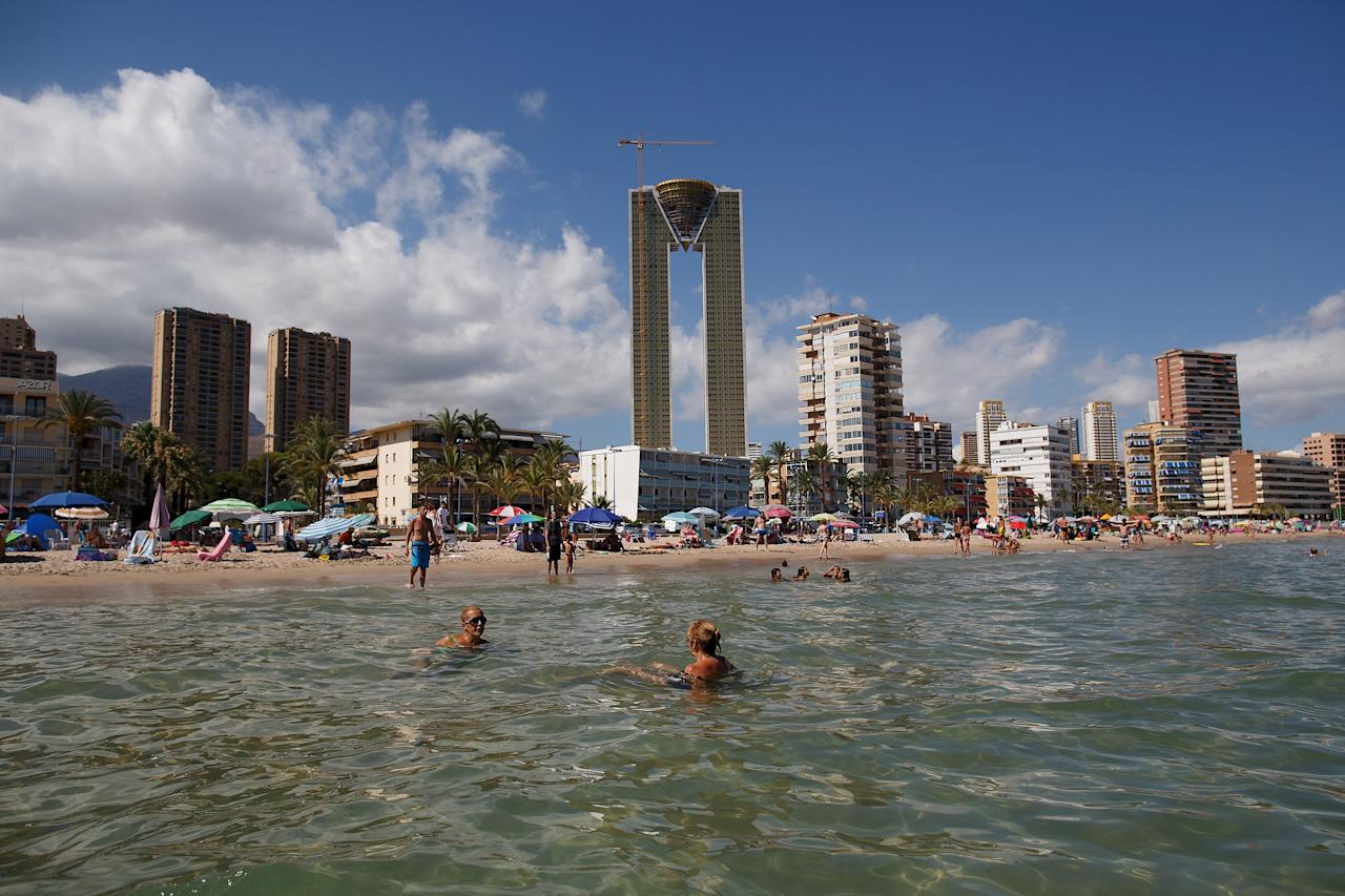 "BENIDORM, SPAIN - AUGUST 09: People swim in the water at Poniente Beach as the unfinished InTempo building stands over them in the distance on August 9, 2013 in Benidorm, Spain. The construction of the In Tempo building began during the economic boom and was meant open in 2009 as the tallest residential building within the E.U. at almost 200 metres high. However after a catalogue of building problems the 47-story twin tower building remains unfinished and has been transferred to the SAREB or ""Bad Bank"". (Photo by Pablo Blazquez Dominguez/Getty Images)"
