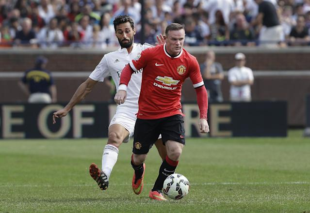 Manchester United forward Wayne Rooney, right, dribbles ahead of Real Madrid defender Alvaro Arbeloa (17) during a Guinness International Champions Cup soccer match at Michigan Stadium in Ann Arbor, Mich., Saturday, Aug. 2, 2014. (AP Photo/Paul Sancya)