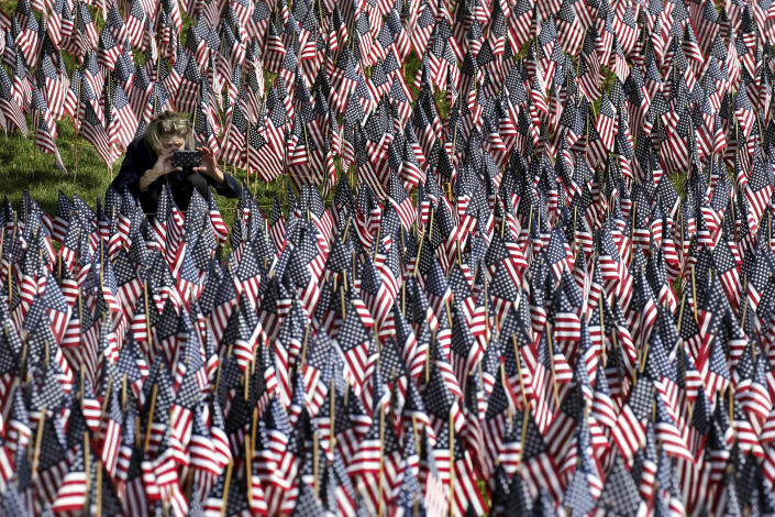 <p>A woman photographs American flags on Boston Common in Boston, which are placed there for Memorial Day on May 24, 2018. The solemn display of tens of thousands of U.S. flags that first appeared on Boston Common a decade ago to honor service members who have died defending the nation is slowly becoming a national movement. The flag gardens, as they are known, can be seen this weekend in Texas, Louisiana, Ohio and New York. (Photo: Elise Amendola/AP) </p>