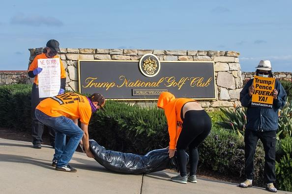 RefuseFascism supporters deliver symbolic home-made body-bags in front of the Trump National Golf Club during an anti-Trump protest.