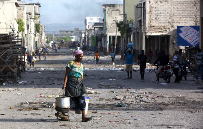 A vendor who sells herbal tea for stomach aches moves to the other side of the street to avoid a shootout between rival gangs fighting for control of the Croix-des-Bossales market, on Boulevard Jean-Jacques Dessalines, a main commercial artery in Port-au-Prince, Haiti, Wednesday, Nov. 21, 2018. The fight for control of the market, where vendors pay the controlling gang regular payments, erupted amid days of protests and a strike against alleged government corruption. (AP Photo/Dieu Nalio Chery)