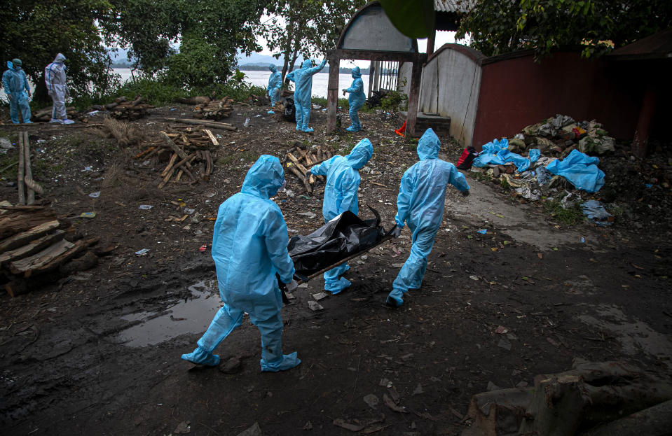 Health workers wearing personal protective equipment carry the body of a COVID-19 victim for cremation in Gauhati, India, Thursday, Sept. 10, 2020. India is now second in the world with the number of reported coronavirus infections with over 5.1 million cases, behind only the United States. Its death toll of only 83,000 in a country of 1.3 billion people, however, is raising questions about the way it counts fatalities from COVID-19. (AP Photo/Anupam Nath)