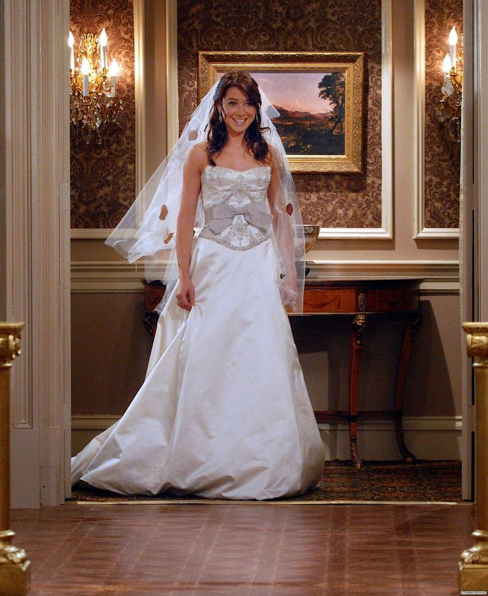 """<p>One of our favorite chapters of <em>How I Met Your Mother </em>was Lily and Marshall's wedding. Nothing on the actual wedding day went right—except for her dress. The silk corseted gown with silver trimmings <a href=""""https://www.eonline.com/photos/11842/how-i-met-your-mother-s-12-most-memorable-fashion-moments"""" rel=""""nofollow noopener"""" target=""""_blank"""" data-ylk=""""slk:designed by Monique Lhuillier"""" class=""""link rapid-noclick-resp"""">designed by Monique Lhuillier</a> was flawless.</p>"""