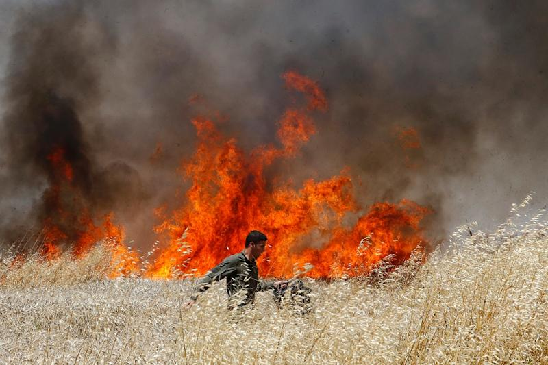 Incendiary kites and balloons launched from Gaza have caused burned large areas of farmland in southern Israel (AFP Photo/JACK GUEZ)