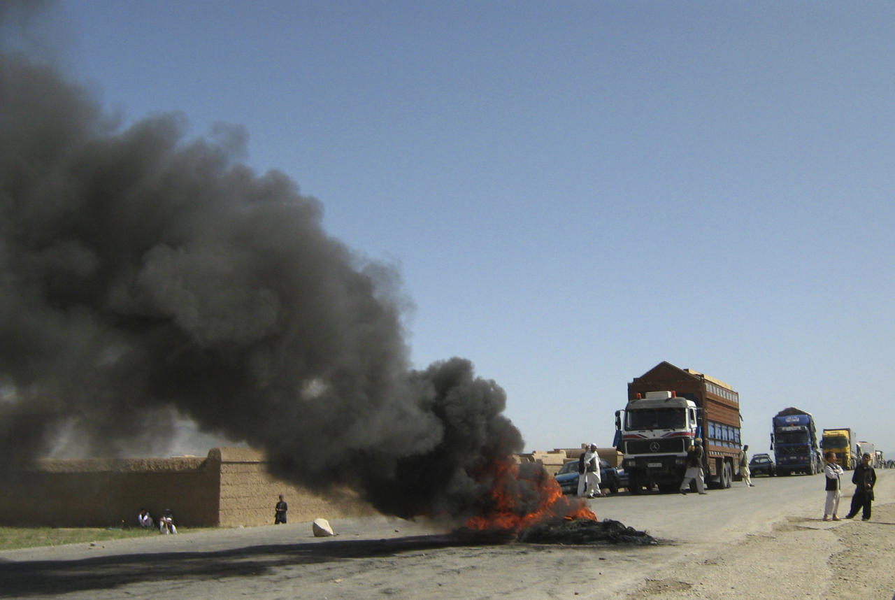 Burning tires block a highway between Kabul and Kandahar in Seed Abad, Wardak province, Afghanistan, Saturday, May 26, 2012. More than 1500 Afghan protesters demanded a stop to military night operations. (AP Photo/Rahmatullah Nikzad)