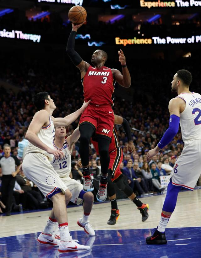 <p> Miami Heat's Dwyane Wade, right, shoots with Philadelphia 76ers' T.J. McConnell, center, and Ersan Ilyasova, left, of Turkey, defend during the first half in Game 2 of a first-round NBA basketball playoff series, Monday, April 16, 2018, in Philadelphia. (AP Photo/Chris Szagola) </p>