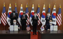 Robert Rapson, Chargé d'Affaires ad interim at U.S. Embassy, left sitting, and South Korea's chief negotiator Jeong Eun-bo, right sit, hold documents as U.S. Secretary of State Antony Blinken, second from left, U.S. Defense Secretary Lloyd Austin, left, South Korean Foreign Minister Chung Eui-yong, second from right, and South Korean Defense Minister Suh Wook, right, clap during an initialing ceremony for Special Measures Agreement at the Foreign Ministry in Seoul, South Korea, Thursday, March 18, 2021. (AP Photo/Lee Jin-man, Pool)