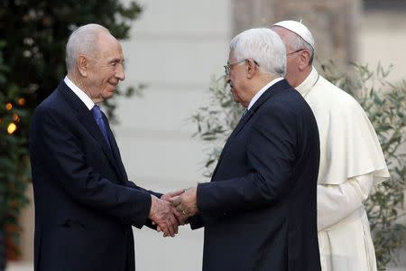 (L-R) Israeli President Shimon Peres shakes hands with Palestinian President Mahmoud Abbas as Pope Francis watches after a prayer meeting at the Vatican June 8, 2014. REUTERS/Max Rossi