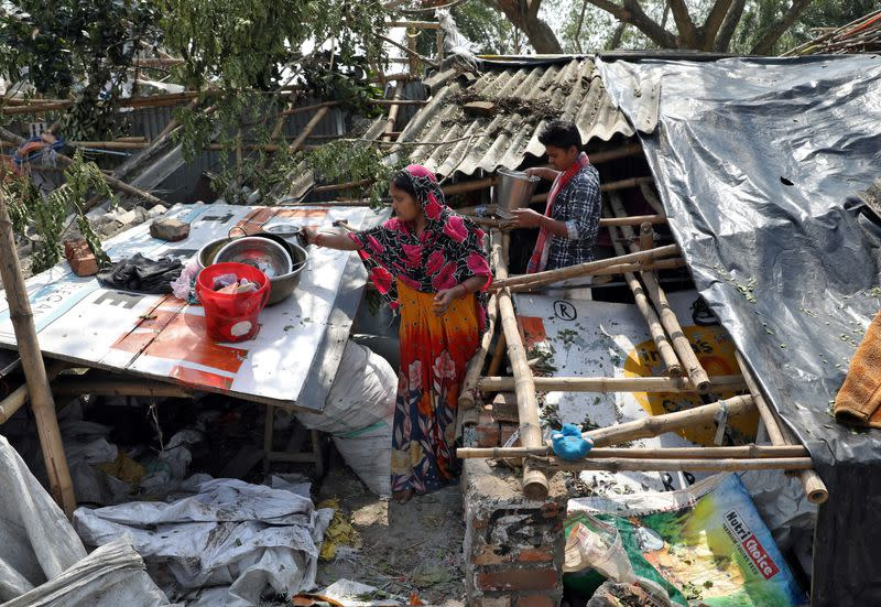 Residents salvage their belongings from the rubble of a damaged house in the aftermath of Cyclone Amphan, in South 24 Parganas district