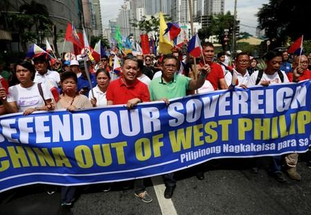FILE PHOTO: Filipino activists and opposition leaders march to protest at the Chinese Embassy in Makati City