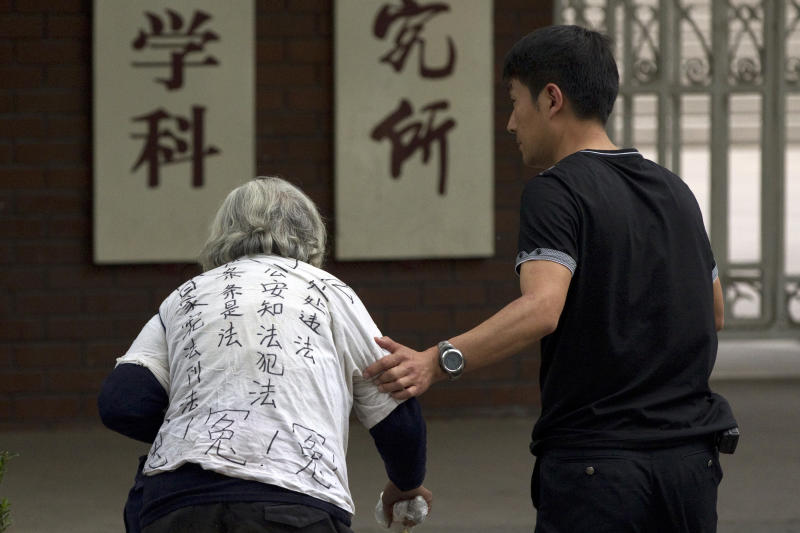 A plain-clothes policeman, right, escorts a petitioner wearing a shirt with written words to protest against alleged injustices outside a hospital where blind Chinese activist Chen Guangcheng is staying for treatment in Beijing, China, Wednesday, May 9, 2012. (AP Photo/Alexander F. Yuan)