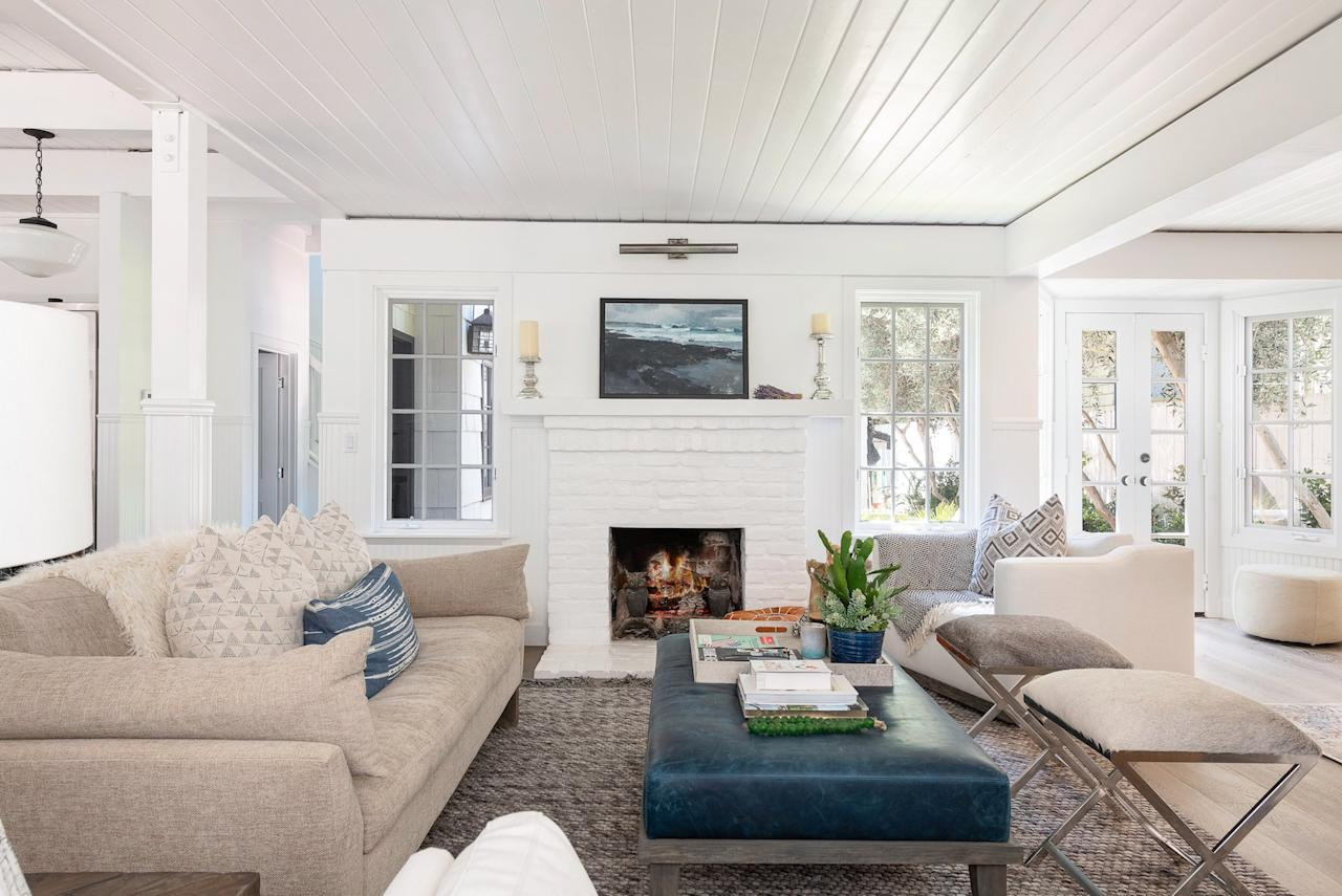 <p>Beachy art and shades of blue continue the ocean-inspired aesthetic in the living room. The open layout lets those in the kitchen keep up the conversation with those lounging in the living room. </p>